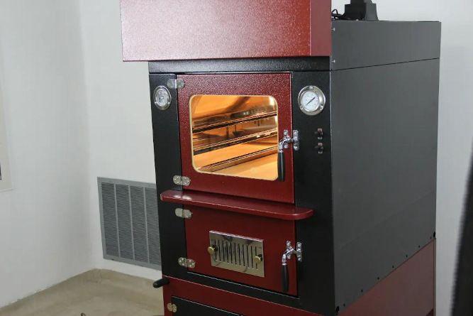 forno a legna da interno di colore rosso e nero con luce e ventilazione accese